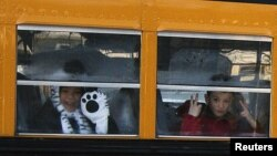 Children from Sandy Hook Elementary School make their way to their new school in Monroe as they leave Newtown, Connecticut, January 3, 2013.
