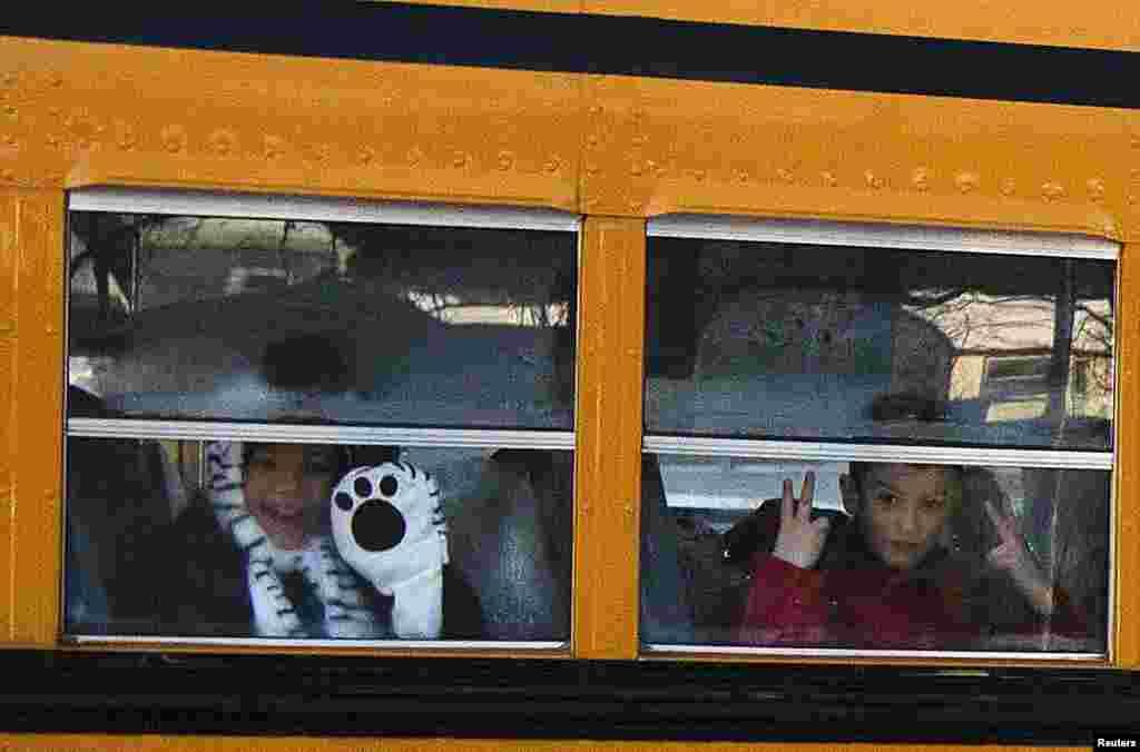 Siswa-siswa Sekolah Dasar Sandy Hook mengintip dari bus sekolah yang membawa mereka ke gedung sekolah yang baru di Monroe, Connecticut.