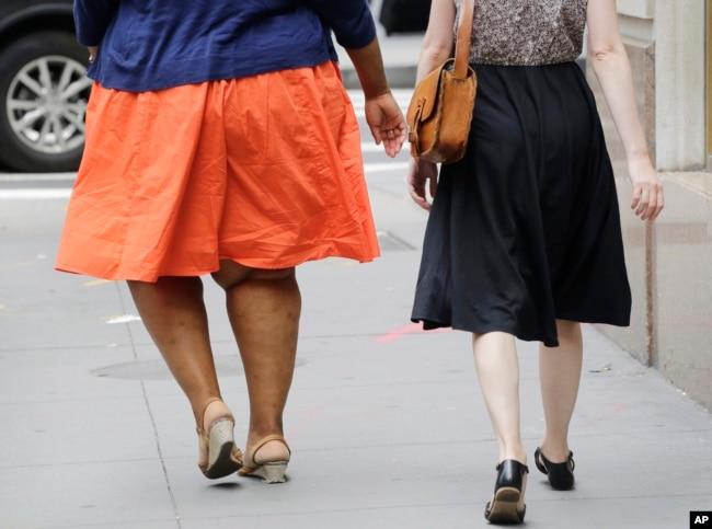 Seorang perempuan dengan masalah berat badan berlebih berjalan di New York, 13 Juli 2015. (Foto: dok)