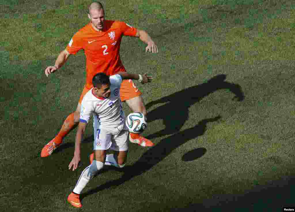 Chile's Alexis Sanchez fights for the ball with Ron Vlaar of the Netherlands during their match at the Corinthians arena in Sao Paulo, June 23, 2014.