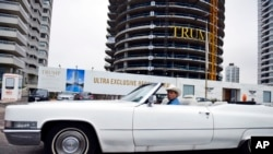 In this Jan. 17, 2017 photo, a man drives a convertible past a Trump Tower under construction in Punta del Este, Uruguay.