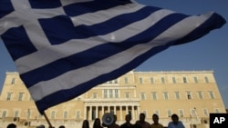 """Protesters raise a Greek flag in front of parliament during a rally against austerity economic measures and corruption in Athens' Syntagma (Constitution) square June 17, 2011. The protest, on its 24th day, was organized through a Facebook group called """"Th"""