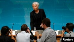 Photographers follow International Monetary Fund Managing Director Christine Lagarde as she arrives to discuss the IMF's annual review of the U.S. economy, in Washington, June 16, 2014.