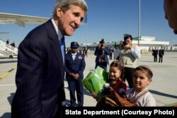 Children greet Kerry with traditional gifts of bread and salt at Turkmenistan's Ashgabat International Airport, Nov. 3, 2015.