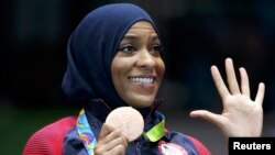FILE - Fencer Ibtihaj Muhammad of the United States displays her bronze medal at the Rio Olympics in Rio de Janeiro, Brazil, Aug. 13, 2016.
