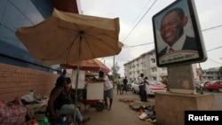 FILE - A street vendor sits near a portrait of Equatorial Guinea's President Teodoro Obiang Nguema Mbasogo in Malabo.