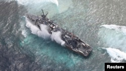 FILE - The USS Guardian, a U.S. Navy minesweeper, is seen at the Vicinity of South Islet in Tubbataha Reefs after it ran aground in Palawan province, west of Manila January 19, 2013 in this handout picture distributed by the Armed Forces of the Philippine