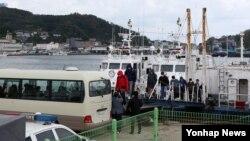 28일 경북 울진 후포항에 도착한 391흥진호 선원이 얼굴을 가린 채 배에서 내려 버스에 타고 있다.