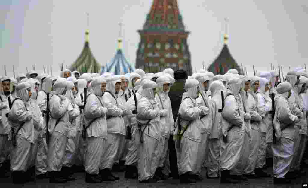 Russian soldiers wear snow gear over Red Army World War II uniforms as they prepare to parade in Red Square in front of St. Basil Cathedral in Moscow, Russia. Thousands of soldiers and military cadets marched across Red Square to mark the 72nd anniversary of a historic World War II parade. The show honored the participants of the Nov. 7, 1941 parade who headed directly to the front lines to defend Moscow from the Nazi forces.