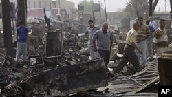 People inspect the scene of rocket attack at a residential complex in Baghdad, July 5, 2011