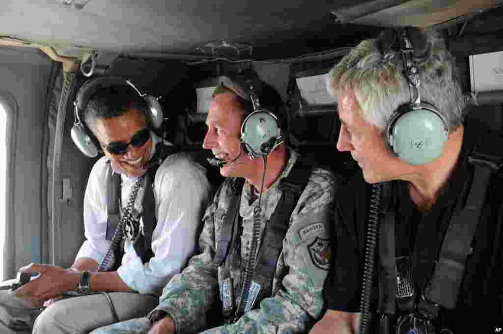 In this photo released by the U.S. army, then Democratic presidential candidate Barack Obama, David Petraeus, and Chuck Hagel, ride in a helicopter, Baghdad, Iraq, July 21, 2008.