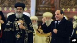 Egyptian President Abdel-Fattah el-Sissi, right, speaks to Coptic Christians as Coptic Pope Tawadros II looks on, during old calendar Christmas Eve Mass at the new Cathedral of the Nativity of Christ, outside Cairo, Egypt, Jan. 6, 2019.