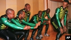 FILE - Dudley Stokes, captain of the Jamaican bobsled team for the Nagano Winter Olympics (R), smiles back at his team members as they demonstrate the bobsled pushing form during a sending-off reception for the team at a Tokyo hotel, Feb. 4, 1998.