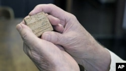 Robert Biggs, professor emeritus at the University of Chicago, holds an Old Akkadian text tablet that was used in the research and assembly of the university's Assyrian Dictionary at the school's Oriental Institute in Chicago, May 28, 2011