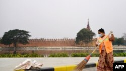 A cleaner wearing a face mask sweeps a road near the ramparts of the former royal palace