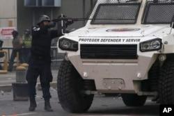 Un officier de police vise son arme lors de manifestants antigouvernementaux à Caracas, au Venezuela, 19 Avril, 2017. Des dizaines de milliers d'opposants du président Nicolas Maduro ont envahi les rues de Caracas dans ce qui a été surnommé la « mère de toutes les marches » contre t