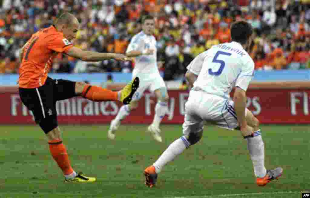 Netherlands' Arjen Robben, left, fires a shot past Slovakia's Radoslav Zabavnik, right, and scores his side's opening goal during the World Cup round of 16 soccer match between the Netherlands and Slovakia at the stadium in Durban, South Africa, Monday,