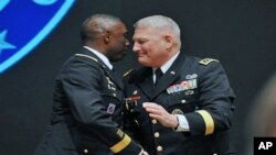 Outgoing Africa Command commander US General William Ward, left, shakes hands with his successor US commander General Carter Ham during the AFRICOM change of command ceremony in Sindelfingen near Stuttgart, March 9, 2011