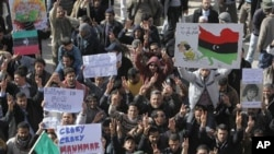 Libyan protesters hold signs and shout slogans against Libyan Leader Moammar Gadhafi during a demonstration, in Tobruk, February 23, 2011