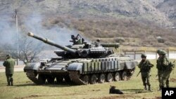 Soldados russos junto a tanque na antiga base ucraniana de Perevalne, na Crimeia