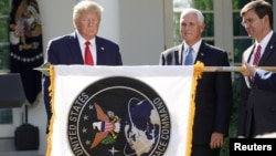 U.S. President Donald Trump stands behind a U.S. Space Command flag with Vice President Mike Pence and Defense Secretary Mark Esper. Launch of the United States Space Command at the White House, August 29, 2019.
