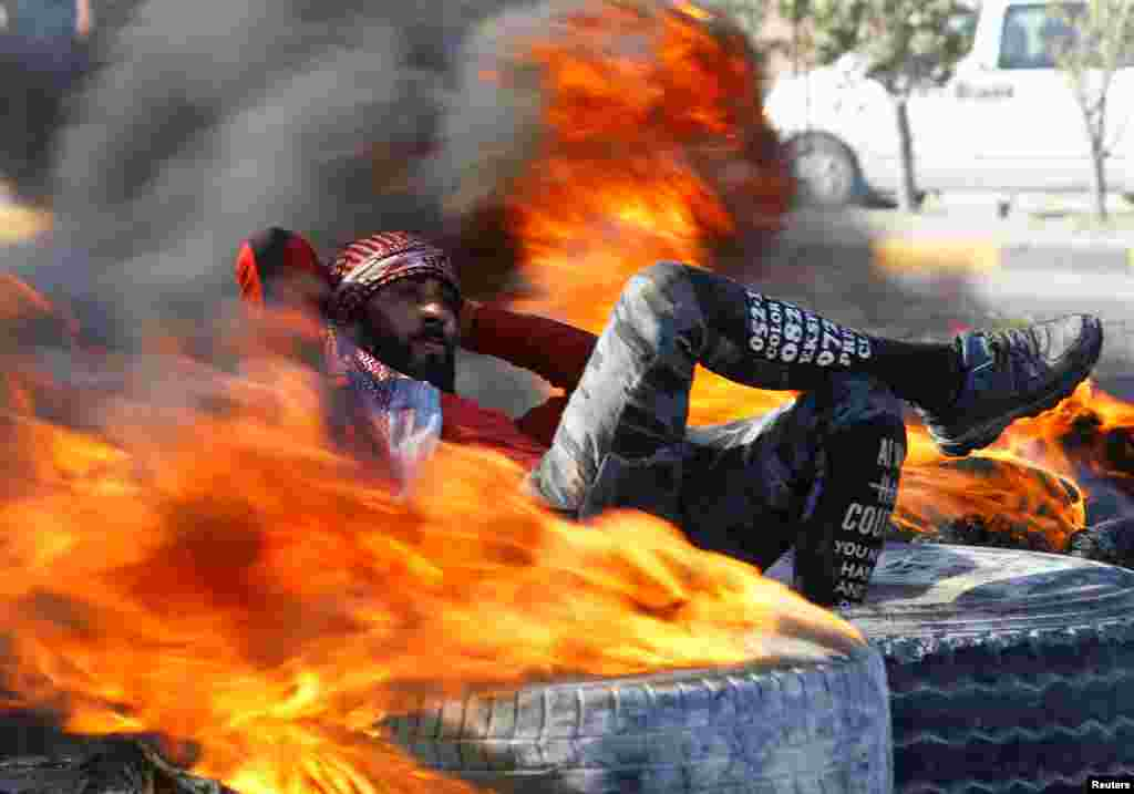 An Iraqi demonstrator sits amid burning tires blocking a road during ongoing anti-government protests in Najaf.