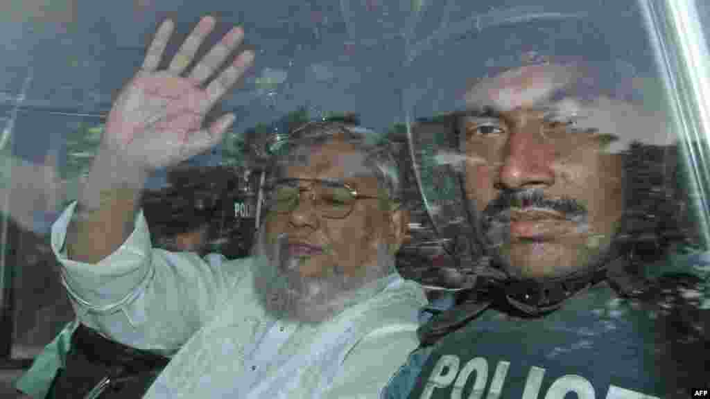 Secretary General of Jamaat-e-Islami Ali Ahsan Mohammad Mujahid waves from a police vehicle as he is transported to the central jail following his court verdict in Dhaka, Bangladesh, July 17, 2013.