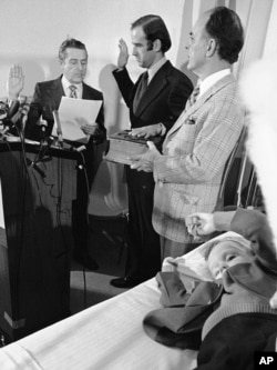 FILE - Four-year-old Beau Biden, foreground, plays near his father, Joe Biden, center, as he is sworn in as the U.S. senator from Delaware, by Senate Secretary Frank Valeo, left, in ceremonies in a Wilmington hospital, Jan. 5, 1973.