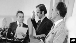 FILE - Four-year-old Beau Biden, foreground, plays near his father, Joe Biden, center, as he is sworn in as the U.S. senator from Delaware, by Senate Secretary Frank Valeo, left, in ceremonies in a Wilmington hospital, Jan. 5, 1973. Beau was injured in an