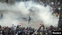 Cảnh sát chống bạo động bắn hơi cay vào người biểu tình trong cuộc đụng độ tại quảng trường Tahrir ở Cairo, 23/11/2012
