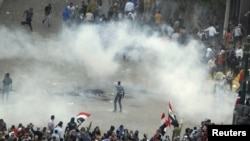 Para pengunjuk rasa berlarian menghindari semprotan gas air mata yang digunaoakn oleh polisi anti huru-hara di untuk membubarkan massa di lapangan Tahrir, Kairo (23/11)
