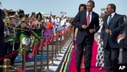 President Barack Obama, followed by first lady Michelle Obama, does a dance upon his arrival ceremony with Tanzanian President Jakaya Kikwete, right, July 1, 2013, at Julius Nyerere International Airport in Dar Es Salaam, Tanzania.