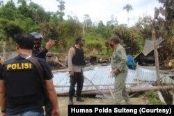 Polisi memeriksa bangunan yang dibakar dalam serangan kelompok teroris Mujahidin Indonesia Timur (MIT) pimpinan Ali Kalora di Dusun Lewonu, Desa Lemban Tongoa, Kecamatan Palolo, Kabupaten Sigi, Sulawesi Tengah, Sabtu (28/11/2020). (Foto: Courtesy/Humas Po