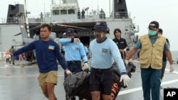 Indonesian's Navy personnel carry a bag containing a dead body of a passenger of AirAsia Flight 8501 at sea off the coast of Pangkalan Bun, Indonesia, Saturday, Jan. 3, 2015.