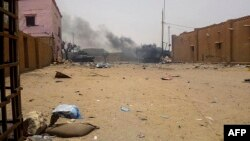 Smoke billows from an army armored vehicle in Gao after and explosion on July 1, 2018.