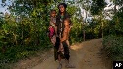 一名罗兴亚穆斯林妇女带着她的两个孩子在去往位于孟加拉的一处难民营的路上。