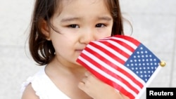 FILE - Megyn Shahi, 2, whose mother is from Nepal, holds onto a U.S. flag during a naturalization ceremony in Washington.