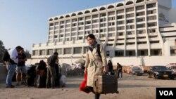 卡拉奇丽晶广场酒店火灾后一名外国游客提着行李离开