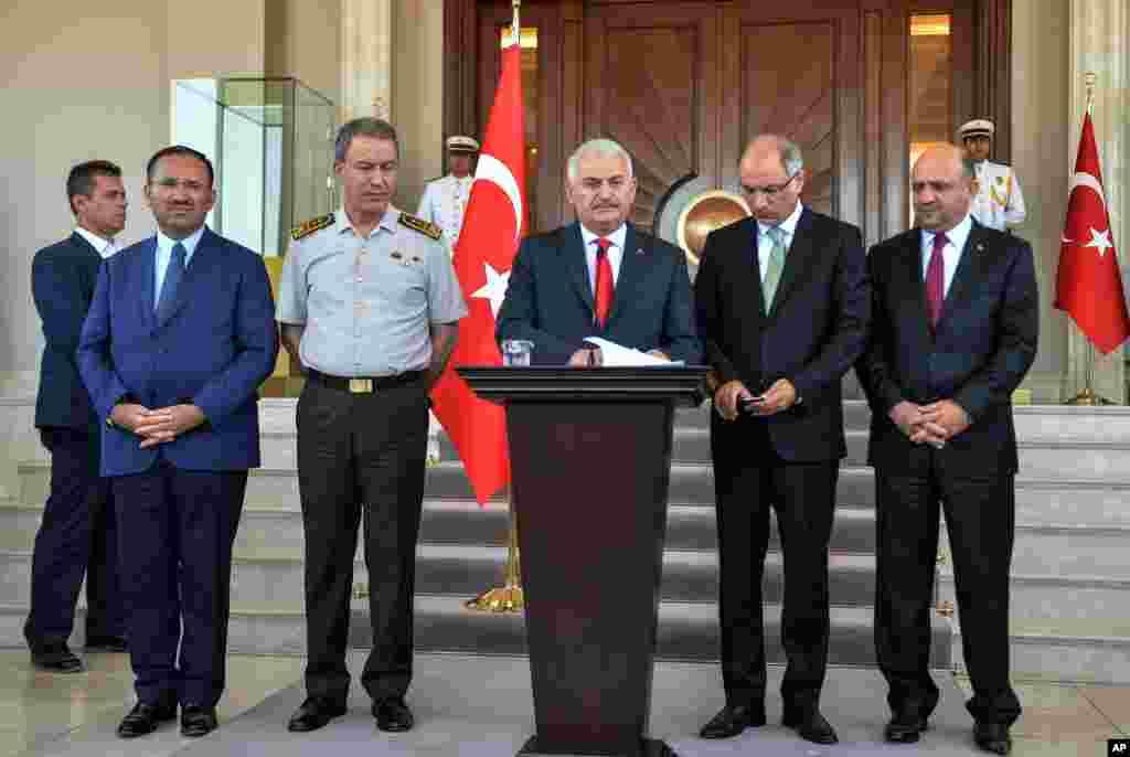 Turkey's Prime Minister Binali Yildirim, center, Chief of Staff Gen. Hulusi Akar, center left, Justice Minister Bekir Bozdag, left, Interior Minister Efkan Ala, second right, and Defense Minister Fikri Isik attend a press conference in Ankara, Turkey, Sat