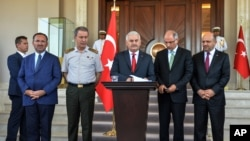 Turkey's Prime Minister Binali Yildirim, center, Chief of Staff Gen. Hulusi Akar, center left, Justice Minister Bekir Bozdag, left, Interior Minister Efkan Ala, second right, and Defense Minister Fikri Isik attend a press conference in Ankara, July 16, 2016.