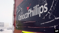 This Feb. 9, 2016, photo shows an ice covered ConocoPhillips sign at the Colville-Delta 5, or as it's more commonly known, CD5, drilling site on Alaska's North Slope.