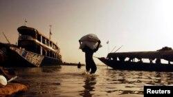Un travailleur apporte des céréales devant être transportées en pirogue sur le fleuve Niger, à Mopti, le 7 février 2007.