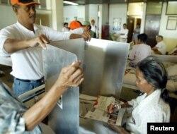 Seorang pasien dibantu petugas untuk melaksanakan hak pilihnya saat pemilu di sebuah rumah sakit di Jakarta, 5 Juli 2004. (Foto: Reuters/arsip))