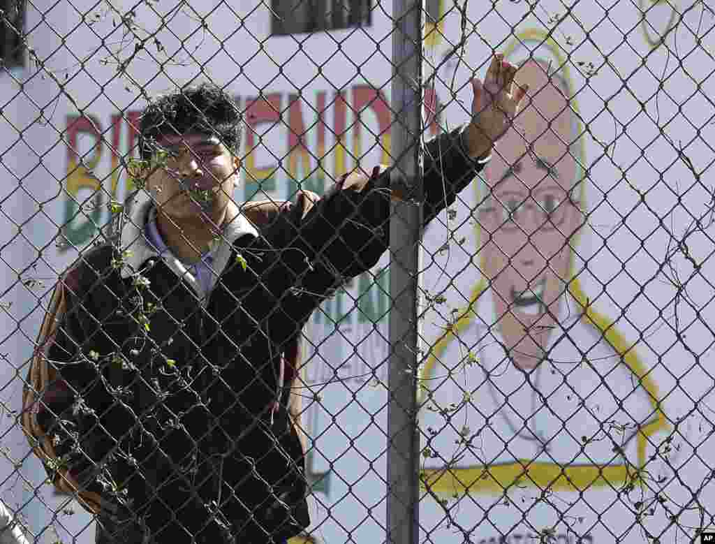 """An inmate stands behind the fence at Palmasola prison, decorated with a mural of Pope Francis that reads in Spanish: """"Welcome who comes in the name of the Lord"""" as the pontiff visited prisoners in Santa Cruz, July 10, 2015."""