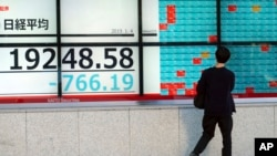 A man looks at an electronic stock board showing Japan's Nikkei 225 index at a securities firm in Tokyo Friday, Jan. 4, 2019.