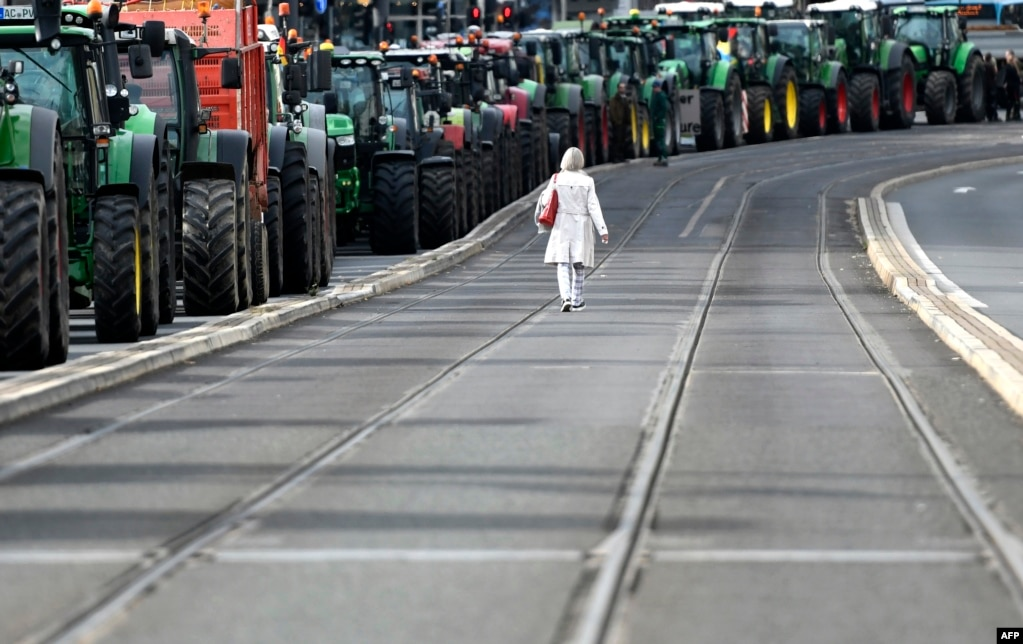 A woman walks past tractors as farmers protest against the government's agricultural policy, including plans to discontinue the use of glyphosate pesticides and to introduce more animal protection, during a demonstration in Bonn, western Germany.