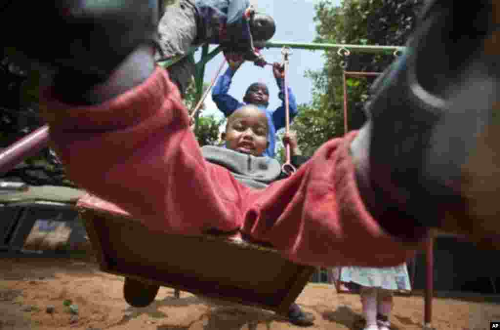 Children play on the swings during playtime at the Nyumbani Children's Home for children with HIV, in Karen on the outskirts of Nairobi, Kenya Wednesday, Nov. 30, 2011. The orphanage, which is heavily reliant on foreign donations, cares for over 100 child