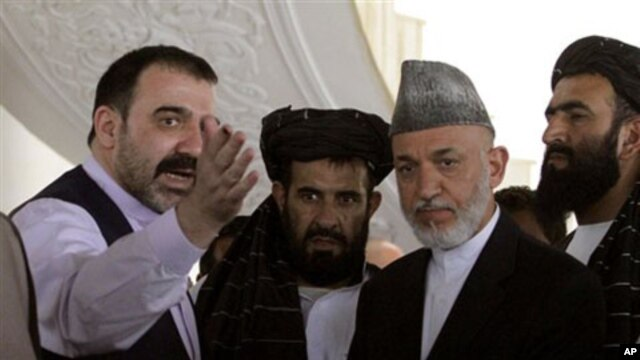 Afghan President Hamid Karzai, second from right, is met by his half brother Ahmad Wali Karzai, left, in Argandab district of Kandahar province, south of Kabul, 09 Oct 2010