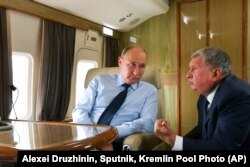 FILE - Russian President Vladimir Putin, left, listens to Russian Rosneft CEO Igor Sechin during his flight to visit Chernigovets coal mine, in Beryozovsky, Kemerovo region, Russia, Monday, Aug. 27, 2018.