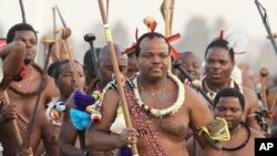 FILE - King Mswati III, front in traditional garb, dances during a Reed Dance in Mbabane, Swaziland, Sept. 3, 2012.